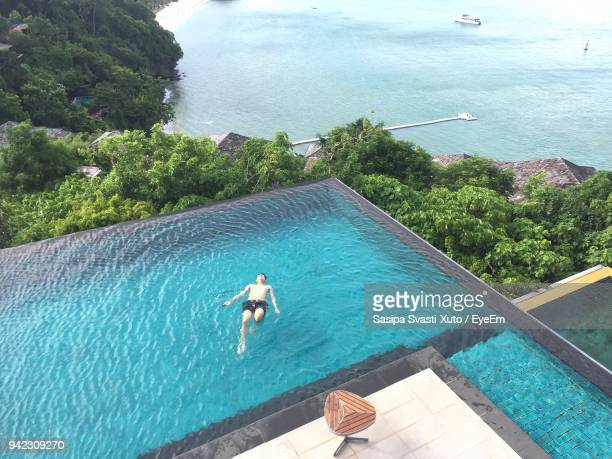 high angle view of man swimming in infinity pool - infinity pool foto e immagini stock