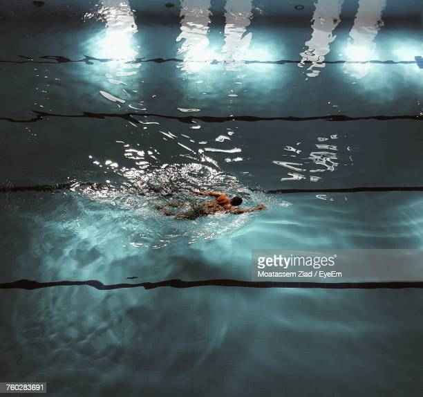 high angle view of man swimming in pool - 室内プール ストックフォトと画像