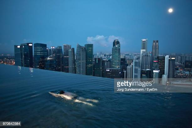 high angle view of man swimming in pool - infinity pool foto e immagini stock