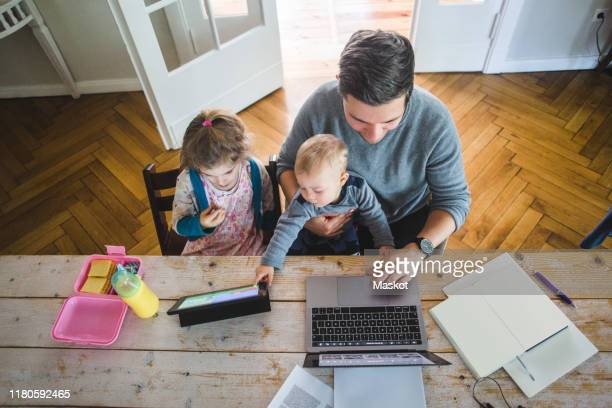 high angle view of man using laptop while sitting with cute son by daughter looking at digital tablet - homemaker stock pictures, royalty-free photos & images