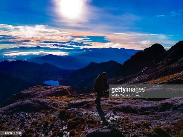 high angle view of man walking cliff against cloudy sky - wally yegiora stock photos and pictures