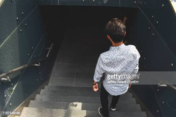 high angle view of man walking down staircases - jeffrey roque stock photos and pictures