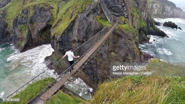 high angle view of man walking on bridge over sea - belfast stock pictures, royalty-free photos & images