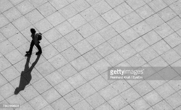 High Angle View Of Man Walking On Footpath During Sunny Day