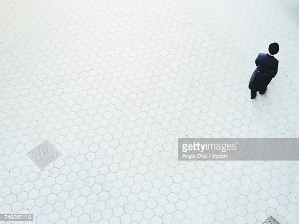 High Angle View Of Man Walking On Footpath In City