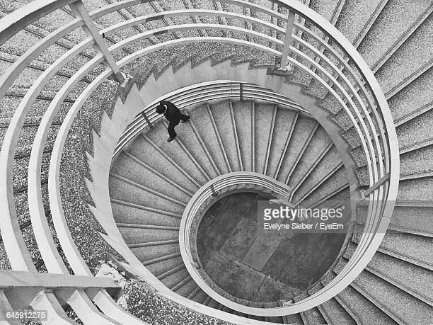 High Angle View Of Man Walking On Spiral Staircase