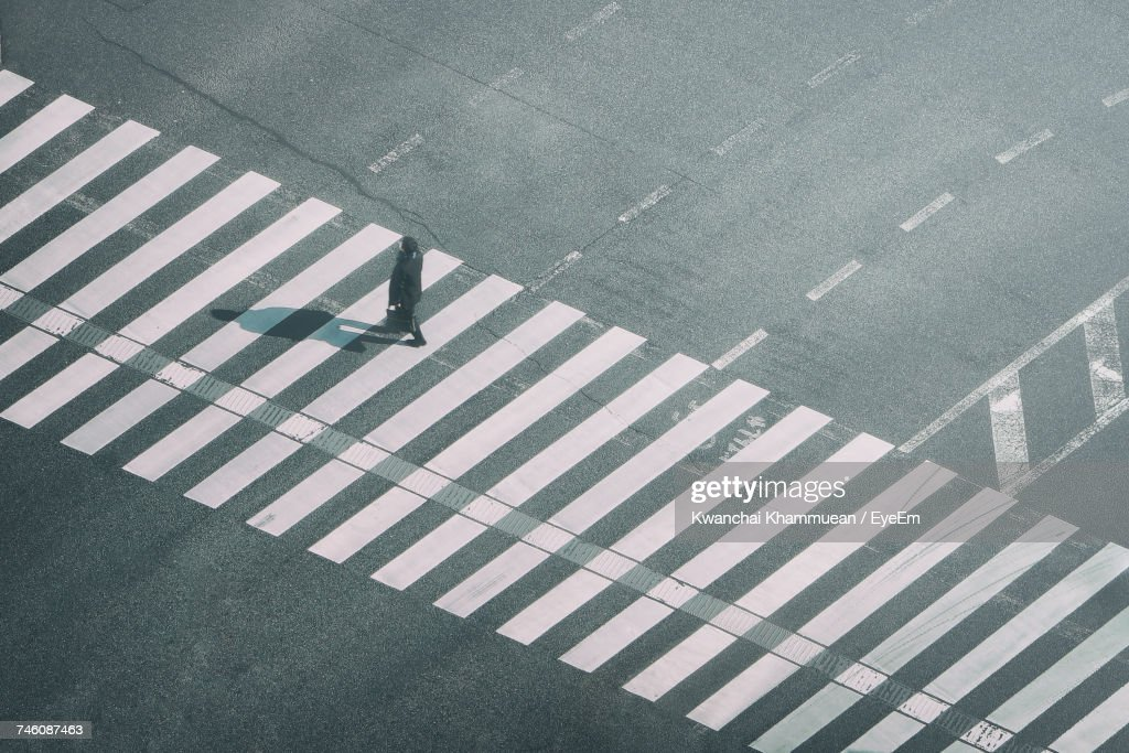 High Angle View Of Man Walking On Zebra Crossing : Stock Photo