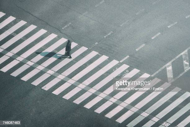 high angle view of man walking on zebra crossing - pedestrian crossing stock photos and pictures