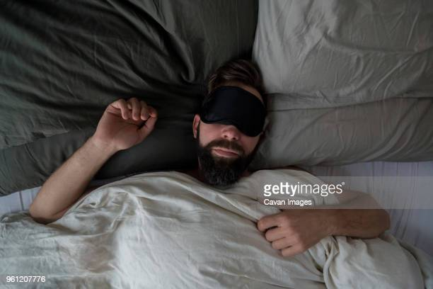 high angle view of man wearing sleep mask while sleeping on bed at home - slapen stockfoto's en -beelden