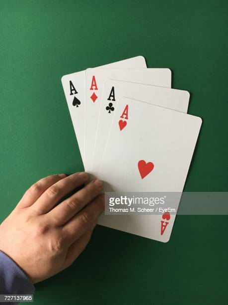 High Angle View Of Man With Aces Cards On Green Table