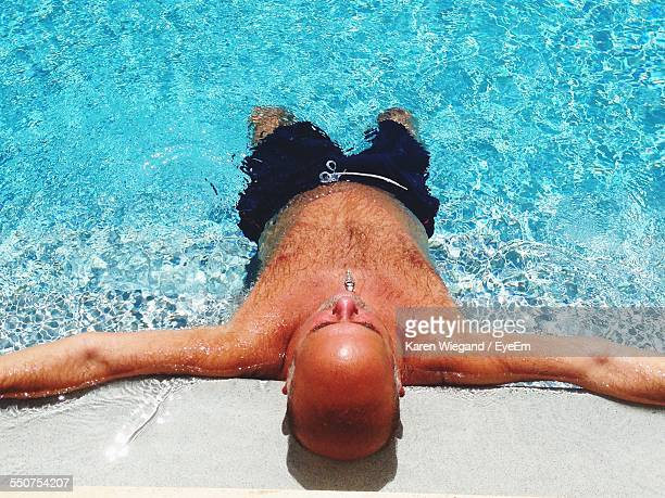 High Angle View Of Man With Arms Outstretched Relaxing In Swimming Pool
