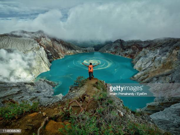 high angle view of man with arms outstretched standing on mountain by lake against cloudy sky - java indonesia fotografías e imágenes de stock