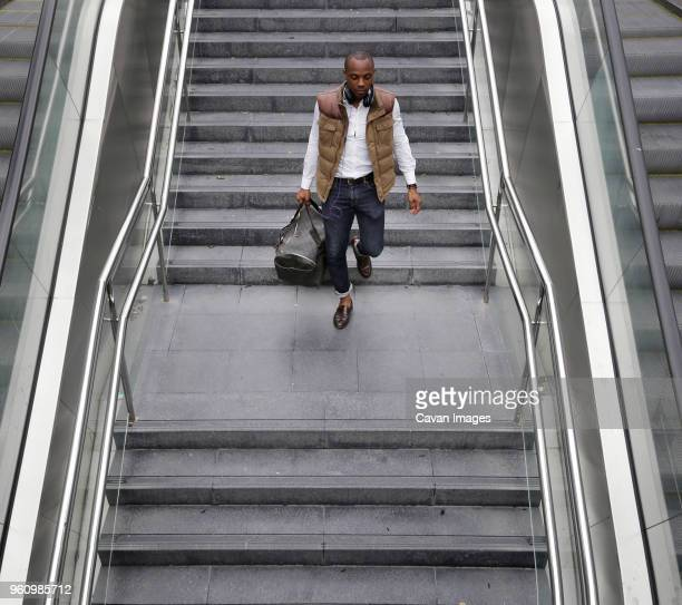 high angle view of man with bag walking on steps at subway station - movimiento hacia abajo fotografías e imágenes de stock