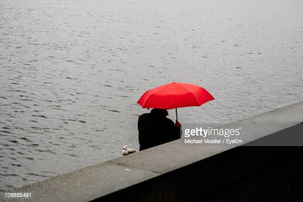 High Angle View Of Man With Red Umbrella By Retaining Wall Against Lake