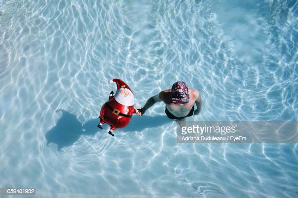 High Angle View Of Man With Santa Claus Balloon In Swimming Pool