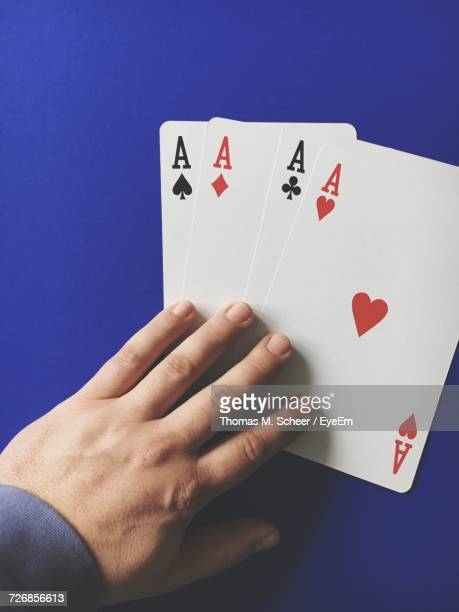 High Angle View Of Man With Three Aces Cards On Blue Table