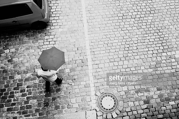 High angle view of man with umbrella walking on cobblestone street