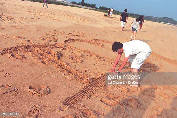 High Angle View Of Man Writing In Sand