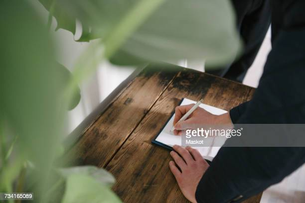 High angle view of man writing on document at home