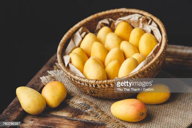 High Angle View Of Mangoes In Basket With Burlap On Wooden Table Over Black Background
