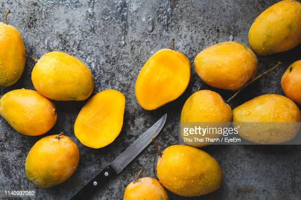 high angle view of mangoes in bowl on table - mango stock-fotos und bilder