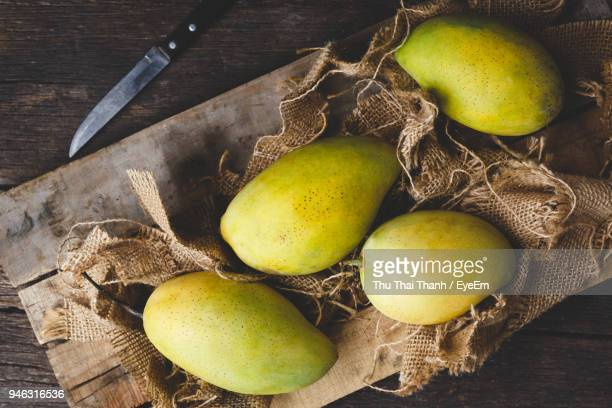 High Angle View Of Mangoes On Cutting Board Over Table