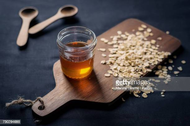 High Angle View Of Maple Syrup In Jar On Cutting Board With Oats At Table