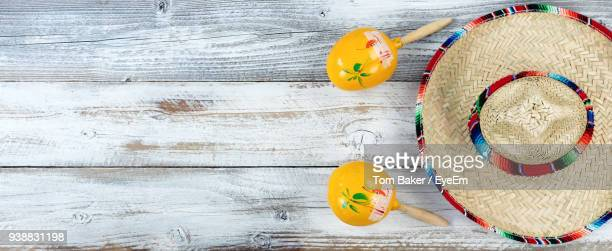 high angle view of maracas with hat on wooden table - mexican hat stock pictures, royalty-free photos & images