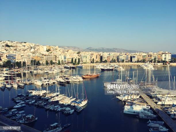 high angle view of marina and buildings against clear sky - piraeus stock photos and pictures