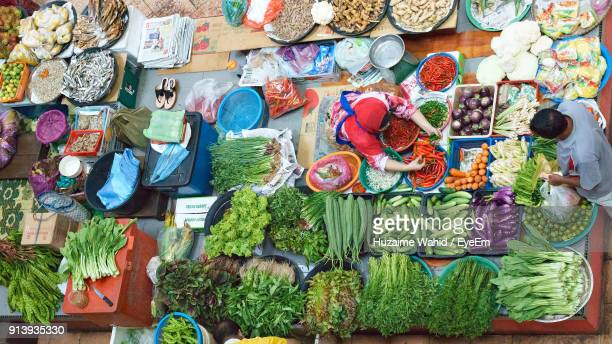 High Angle View Of Market Vendor Selling Vegetables In Market