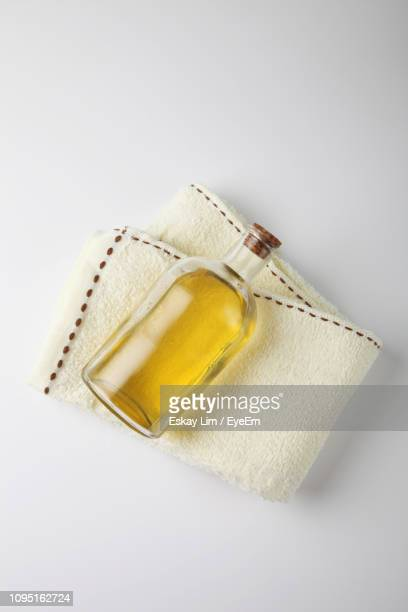 high angle view of massage oil bottle and towel on white background - massage oil stock pictures, royalty-free photos & images