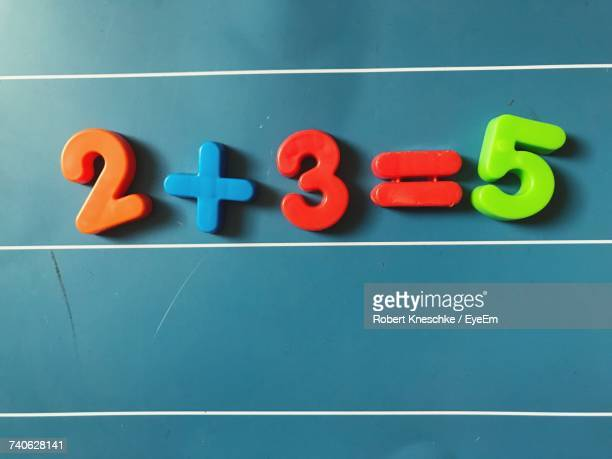High Angle View Of Mathematical Symbol Toys On Blue Table