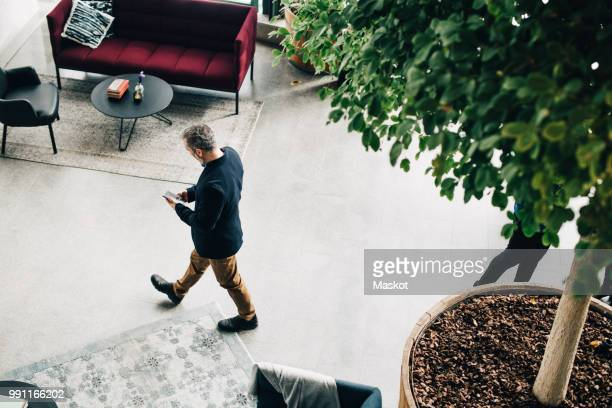 high angle view of mature businessman using mobile phone while walking in office - stockholm stock pictures, royalty-free photos & images