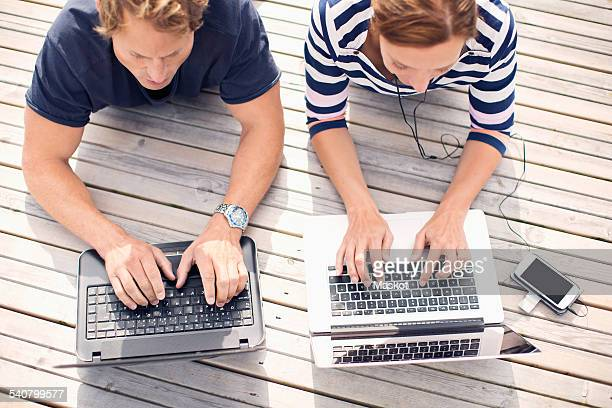 High angle view of mature couple using laptops while lying on pier