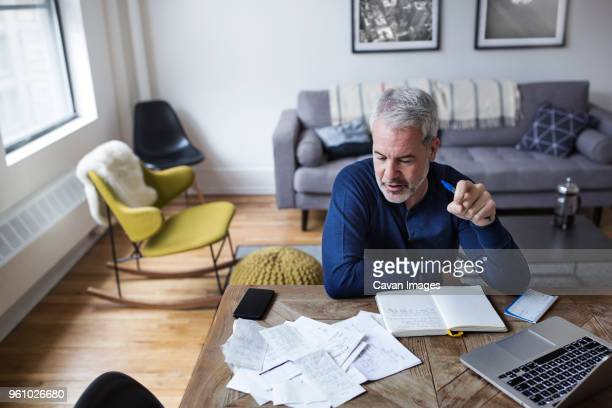 high angle view of mature man analyzing bills at table in home - one mature man only stock pictures, royalty-free photos & images