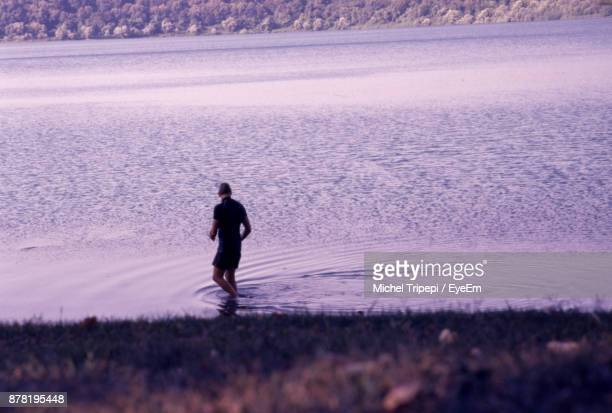 High Angle View Of Mature Man Walking In Lake