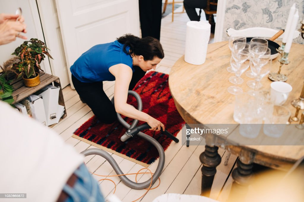 High angle view of mature woman cleaning hardwood floor with vacuum cleaner after party at home : Stock Photo