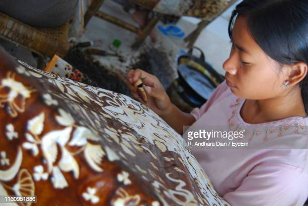 high angle view of mature woman doing design on batik at home - indonesian cloth 個照片及圖片檔