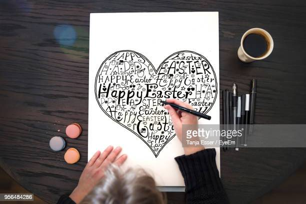 high angle view of mature woman drawing on paper at table during easter - happy easter text stock pictures, royalty-free photos & images