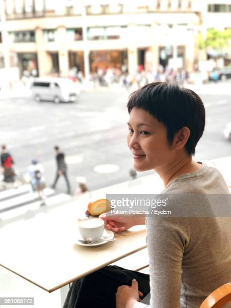high angle view of mature woman having coffee in cafe - 背景に人 ストックフォトと画像