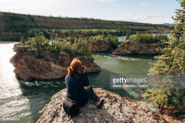 High Angle View Of Mature Woman Sitting On Cliff Against River