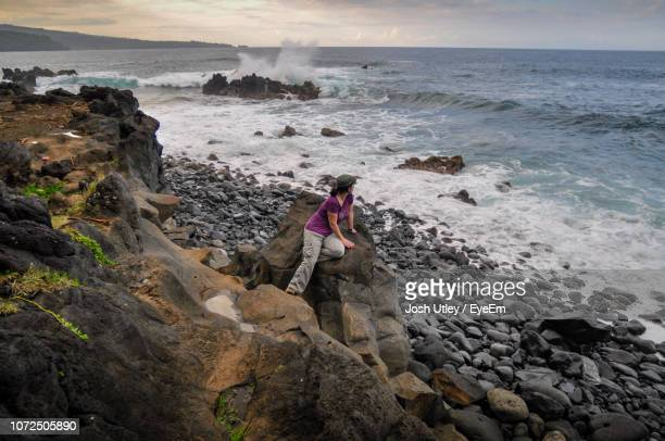 High Angle View Of Mature Woman Sitting On Rock At Beach