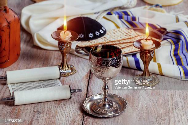 high angle view of matzo with drink and candles on wooden table against wall - happy passover stock pictures, royalty-free photos & images