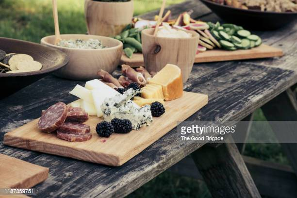 high angle view of meat and cheese platter on table outdoors - kaasplank stockfoto's en -beelden