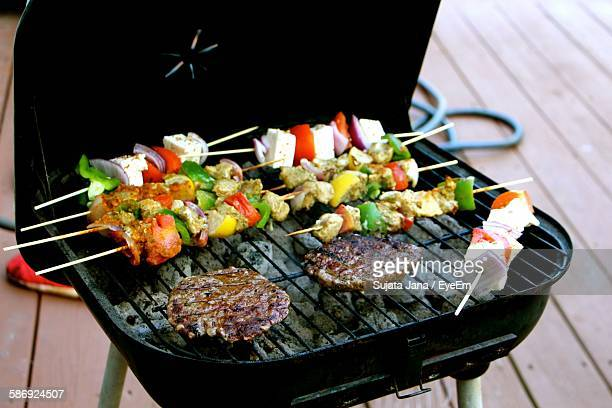 High Angle View Of Meat And Kebabs Grilling On Barbecue