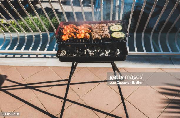 High Angle View Of Meat On Barbecue Grill At Balcony