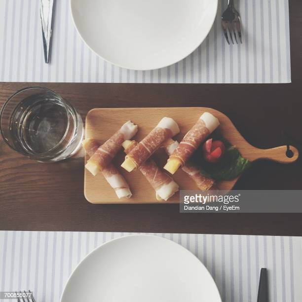 High Angle View Of Meat On Cutting Board Over Table