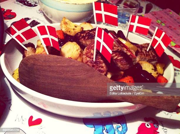 High Angle View Of Meat With Danish Flags Served On Table