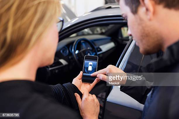 high angle view of mechanic explaining mobile app to customer - klanten georiënteerd stockfoto's en -beelden