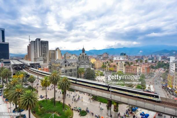high angle view of medellin cityscape with elevated metro train on foreground in antioquia, colombia - medellin colombia fotografías e imágenes de stock
